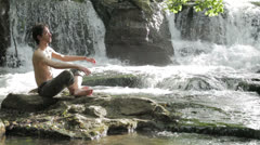 Man makes physical exercises to keep fit , near wonderful waterfalls Stock Footage