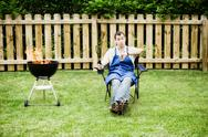 Barbeque: man checks time on watch Stock Photos