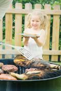 barbeque: girl waits for hot dog lunch - stock photo