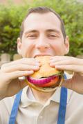 Barbeque: man eating a hamburger Stock Photos