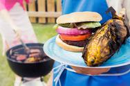 Barbeque: man and woman cook outdoor meal Stock Photos