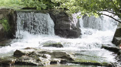 Hiker cross the stream to sit on a rock and write in a notebook - waterfall Stock Footage