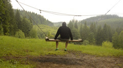 Man swinging on a swing Stock Footage