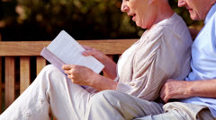 Elderly couple reading a book Stock Footage