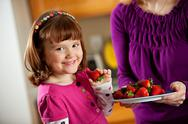 Kitchen girl: taking a berry from a plate Stock Photos