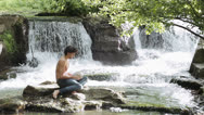 Stock Video Footage of a man writes his thoughts and notes on the nature - touching water