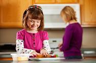 Kitchen girl: making a cheese sandwich Stock Photos