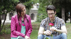 A shy man gives a red rose to a beautiful woman - love - lover- fond - kiss Stock Footage
