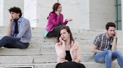 Four young people are on the phone sitting on a staircase - technology Stock Footage