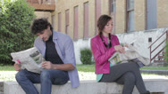 Stock Video Footage of a man and a woman are reading on newspaper