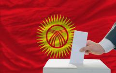 man voting on elections in kyrghyzstan in front of flag - stock photo
