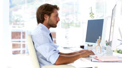 Businessman yawning at his desk Stock Footage