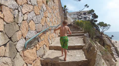 Boy runs up the stairs along the seashore Stock Footage