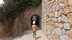 The boy goes through the stone tunnel along the coast Stock Footage
