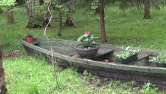 Old  boat with flowerpots in resort park Stock Footage