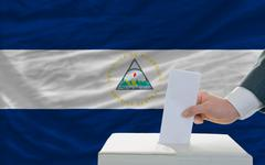 Stock Photo of man voting on elections in nicaragua in front of flag