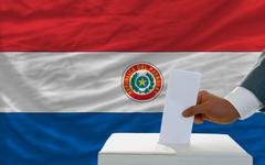 man voting on elections in paraguay in front of flag - stock photo