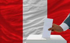 Stock Photo of man voting on elections in peru in front of flag