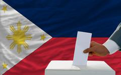 Man voting on elections in phillipines in front of flag Stock Photos