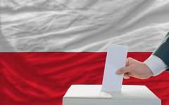 Stock Photo of man voting on elections in poland in front of flag
