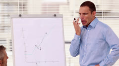 Serious businessman pointing at a chart on a whiteboard Stock Footage