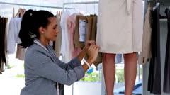 Pretty fashion designer working on a bespoke dress Stock Footage