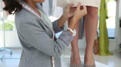 Pretty fashion designer working on a hemline of a dress Stock Footage