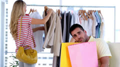 Bored man while his girlfirend is doing shopping Stock Footage