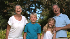 Grandchildren and grandparents posing in a park Stock Footage