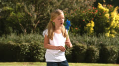 Little girl blowing a pinwheel in her garden - stock footage
