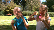 Cheerful siblings having fun with bubbles Stock Footage