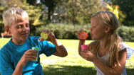 Cheerful siblings having fun together with bubbles Stock Footage