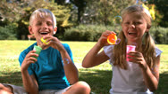 Siblings having fun together with bubbles Stock Footage