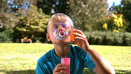 Stock Video Footage of Cheerful young boy blowing into a bubble wand