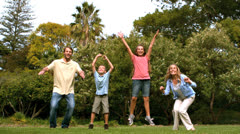 Happy family jumping together Stock Footage