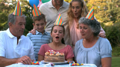 Happy family blowing the candles of birthday cake - stock footage