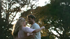 Beautiful young woman leaning in her husband's arms - stock footage