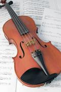 Violin resting on music scores Stock Photos