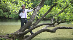 A businessman relaxing near a river and smoking a cigarette Stock Footage
