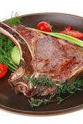 savory : roasted beef spare rib on dark dish with pepper and tomato - stock photo