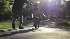 Excited Father Helps Daughter Ride Bike For First Time Stock Footage