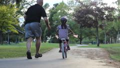 Proud Father Encourages Daughter Riding Her Bike Stock Footage