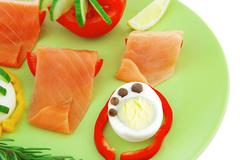 smoked salmon slices on green - stock photo