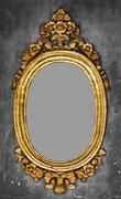 Old-fashioned gilt frame for a mirror on a concrete wall Stock Photos