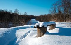 Stock Photo of bench covered with snow in the rural