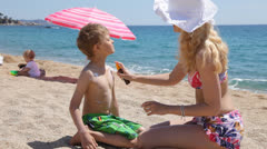 Mother putting sunscreen on her son Stock Footage