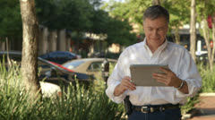 man watching something funny on a tablet smiles at camera - stock footage