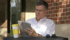 Stock Video Footage of businessman at an outdoor cafe using a tablet pc