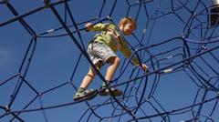 Boy climbing on a playground equipment Stock Footage