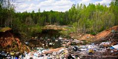 Garbage dump in green forest. wide shot. Stock Photos